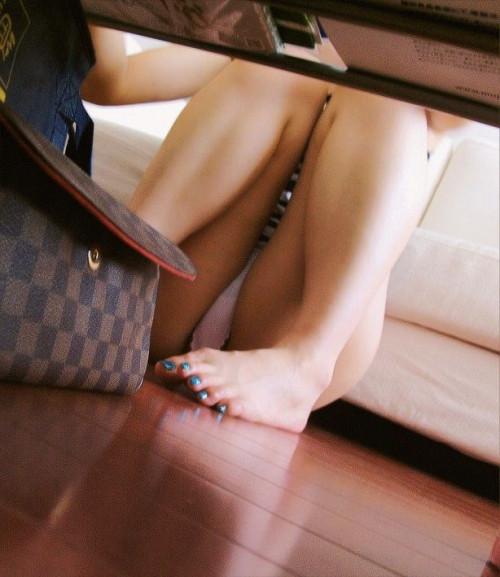 """【盗撮エロ】手に持ったスマホでテーブルの下からこっそり隠し撮りしている""""パンチラ盗撮""""のエロ画像・1枚目"""